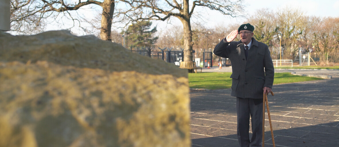 Photograph of Ted saluting in a cemetery.